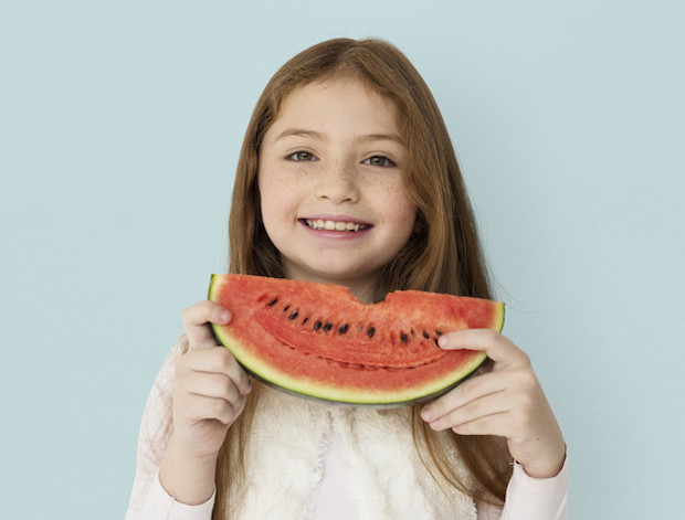 Young cheerful girl holding a slice of watermelon
